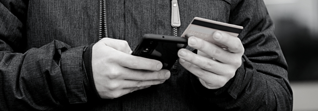 Person accessing digital bank while holding a card and a phone